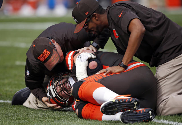 Trainers look at Cleveland Browns tackle Joe Thomas after Thomas was hurt in the second half of Sunday's against the Titans. (AP)