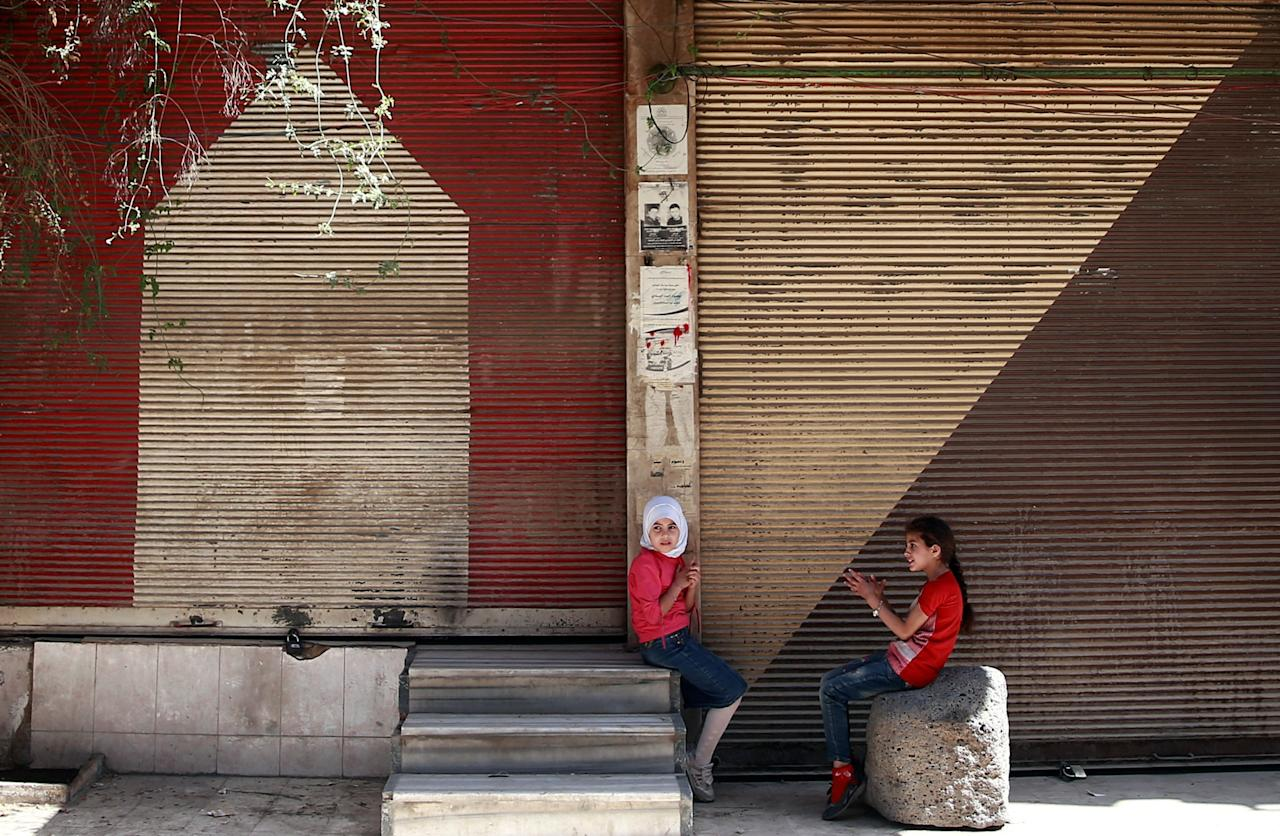 Syrian girls sit in front of shops in the rebel held besieged Douma neighbourhood of Damascus, Syria July 23, 2017. REUTERS/Bassam Khabieh     TPX IMAGES OF THE DAY