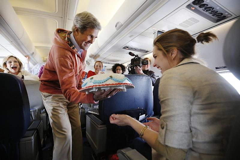 Secretary of State John Kerry presents a birthday cake to traveling CBS correspondent Margaret Brennan, right, during a flight from Kabul to Paris, Tuesday, March 26, 2013. Kerry went to Paris for talks with French officials about aid to the Syrian opposition and the situation in Mali. (AP Photo/Jason Reed, Pool)