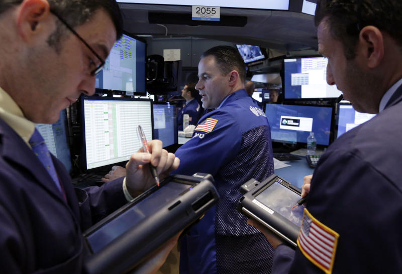 Traders gather at the post of specialist Jason Hardzewicz, center, on the floor of the New York Stock Exchange Monday, April 28, 2014. Stocks are mostly higher in early trading as traders hope for another blockbuster merger in the health-care industry. (AP Photo/Richard Drew)