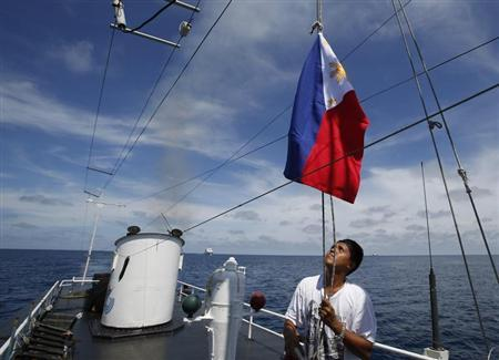 Philippine Navy crew member aboard a civilian supply ship raises a Philippine national flag after ship was able to evade an attempted blockade by Chinese vessels at disputed Second Thomas Shoal in South China Sea