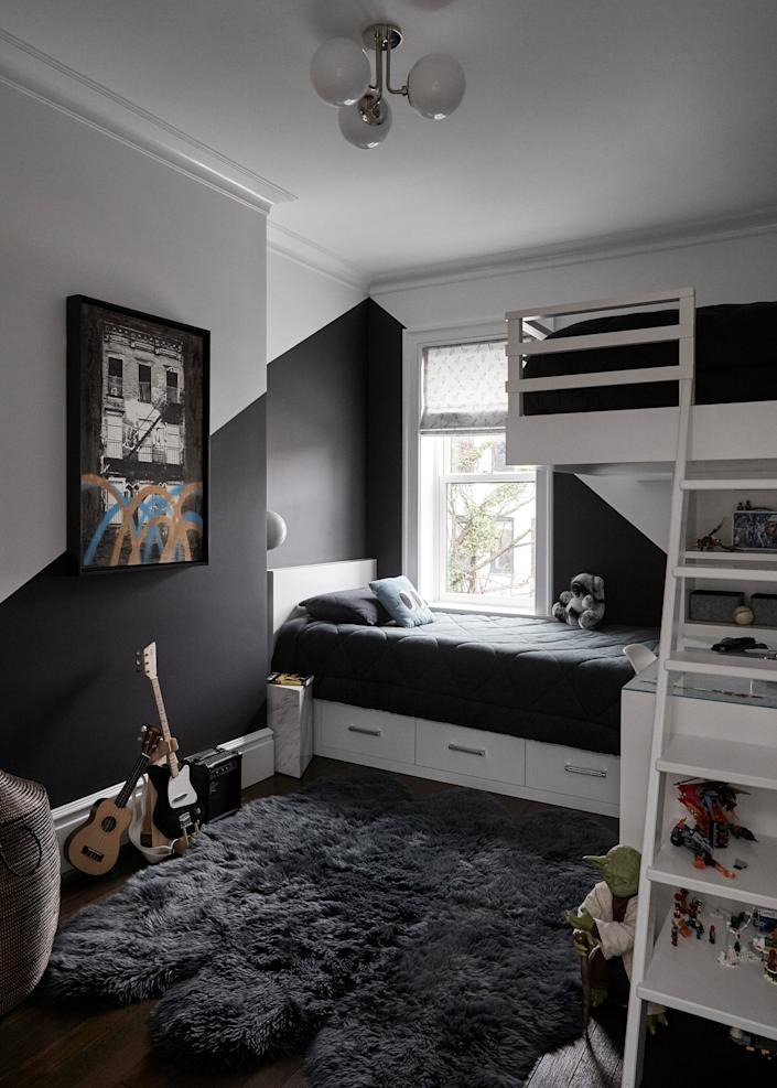 "<div class=""caption""> Custom bunk beds maximize the space in this boys' room. Black paint from <a href=""https://www.benjaminmoore.com/en-us"" rel=""nofollow noopener"" target=""_blank"" data-ylk=""slk:Benjamin Moore"" class=""link rapid-noclick-resp"">Benjamin Moore</a>, a spray-painted artwork bought at a street fair, and rock guitars help set a playful yet masculine vibe. </div>"