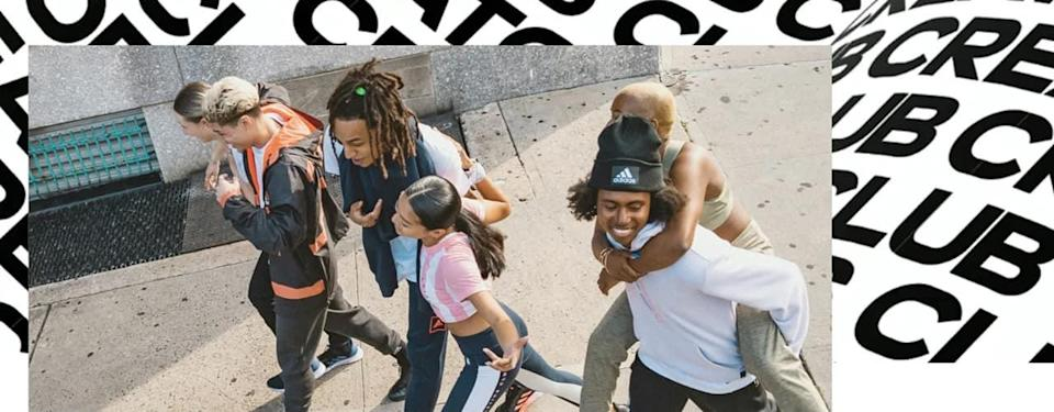 group of people walking, talking and smiling and adidas designer club text behind them