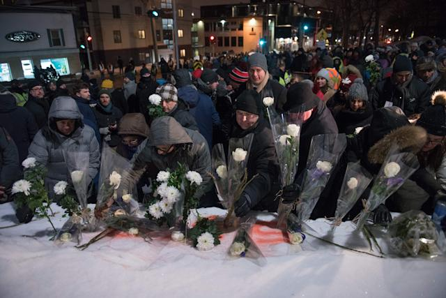 People lay flowers in memory of the victims near the Islamic Cultural Centre in Quebec City on Jan. 29, 2018. (Photo: ALICE CHICHE via Getty Images)