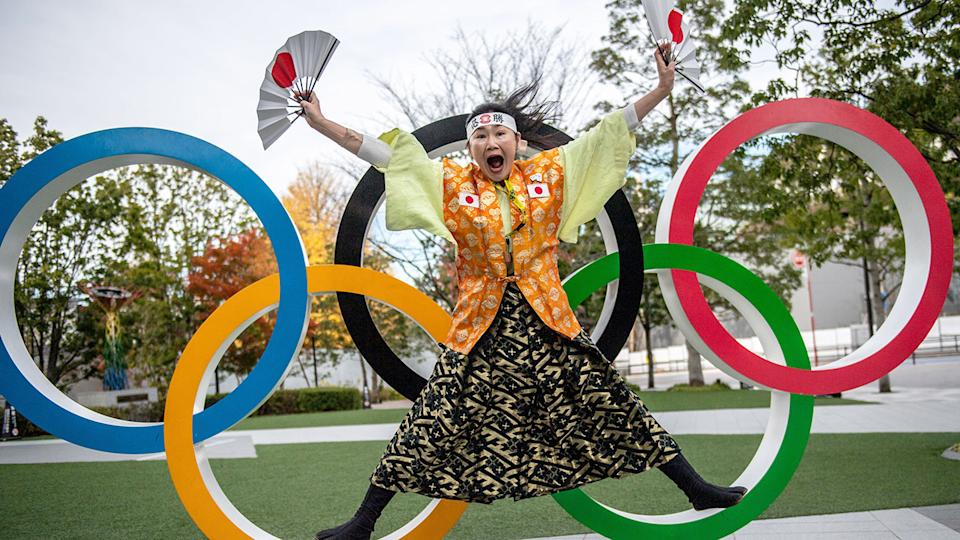 Pictured here, a Japanese woman poses with the Olympic rings in Tokyo.