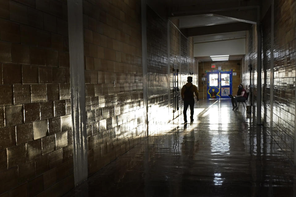 A student walks between classes at Wyandotte High School in Kansas City, Kan., on the first day of in-person learning Wednesday, March 30, 2021. The school, like other schools nationwide, has made extra efforts to keep kids at risk of dropping out engaged as classes went virtual due to the pandemic. (AP Photo/Charlie Riedel)