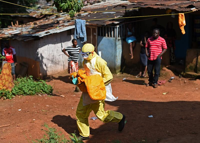 A health worker from Sierra Leone's Red Cross Society Burial Team 7 carries the corpse of a child in the capital Freetown on November 12, 2014 (AFP Photo/Francisco Leong)