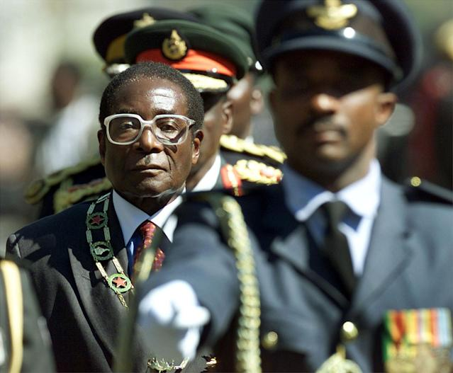<p>Mugabe inspects troops at the opening of Parliament in 2000. The fifth Parliament since independence in 1980 saw the largest opposition to Mugabe's ZANU-PF party, with the Movement for Democratic Change holding 57 seats in the 150-seat chamber. (Photo: Howard Burditt/Reuters) </p>