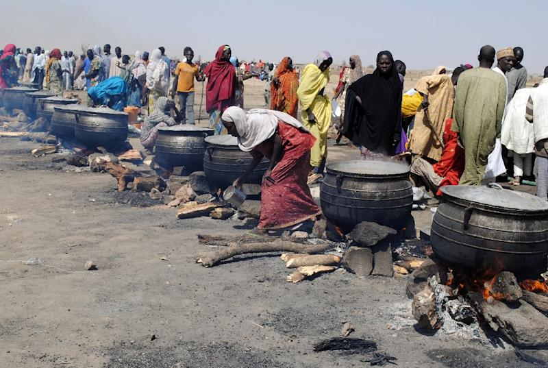 Women cook in pots heated with firewood at Dikwa on February 2, 2016 (AFP Photo/)