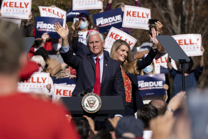 FILE - In this Nov. 20, 2020, file photo Vice President Mike Pence and Kelly Loeffler wave to the crowd during a Defend the Majority Rally in Canton, Ga. U.S. Sen. Kelly Loeffler waves behind Pence. (AP Photo/Ben Gray, File)