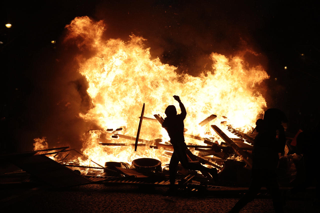 <p>A demonstrator throws debris at a burning barricade while protesting with others against the rising of the fuel taxes on the famed Champs Elysees avenue, in Paris, France, Saturday, Nov. 24, 2018. (Photo: Kamil Zihnioglu/AP) </p>