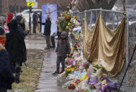Mourners leave bouquets on a fence put up around the parking lot where a mass shooting took place the day before in a King Soopers grocery store Tuesday, March 23, 2021, in Boulder, Colo. (AP Photo/David Zalubowski)