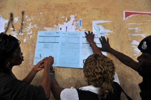 Electoral officers post local election results at a polling station in Freetown, a day after voting