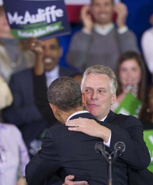 President Barack Obama hugs Virginia Democratic gubernatorial candidate Terry McAuliffe prior to speaking on McAuliffe's behalf at a campaign rally Washington Lee High School in Arlington, Va., Sunday, Nov. 3, 2013. (AP Photo/Cliff Owen)