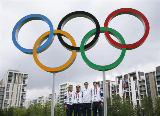British tennis players Laura Robson (L-R), Anne Keothavong, Andy Murray and Jamie Murray pose for photos with the Olympic rings at the athletes village at the Olympic Park in London July 20, 2012.