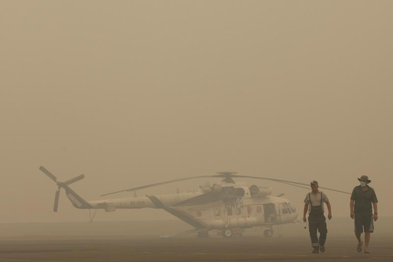 A helicopter crew deployed for water bombing by the National Disaster Management Agency walk past their grounded aircraft due to thick haze in Palembang on Indonesia's Sumatra island on September 30, 2015 (AFP Photo/Abdul Qodir)