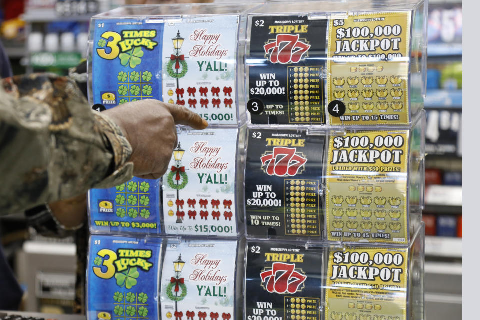 A customer points to the scratch-off ticket she wants to purchase from at a Jackson, Miss., convenience store, Monday, Nov. 25, 2019. Licensed lottery retailers in the state began selling tickets Monday for the first time in the state. The multistate games Powerball and Mega Millions will be available in Mississippi starting Jan. 30. (AP Photo/Rogelio V. Solis)