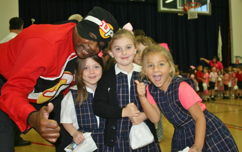 "In this October 2016 picture provided by the Orleans Parish Sheriff's Office longtime aerobatic pilot Franklin Augustus dressed in his ""Drug Fighter"" superhero costume poses with students at a program for school children put on by Sheriff Marlin Gusman. Augustus died Aug. 16, 2019,2019, when the small plane he was piloting crashed shortly after taking off from New Orleans' Lakefront Airport. Popular television anchor Nancy Parker, who was working on a story about Augustus also died in the crash. (Orleans Parish Sheriff's Office via AP)"