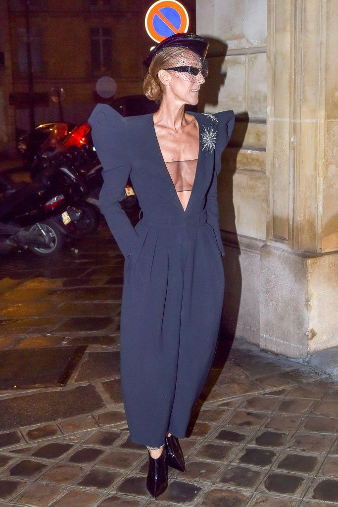 <p>For a night out in Paris, Dion chose a plunging navy jupmsuit with gorgeous exaggerated shoulder detailing. She added a matching hat, sleek black booties, and sunglasses, of course.</p>