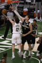 Brooklyn Nets forward Joe Harris (12) shoots next to Milwaukee Bucks center Brook Lopez (11) during the first half of Game 6 of a second-round NBA basketball playoff series Thursday, June 17, 2021, in Milwaukee. (AP Photo/Jeffrey Phelps)