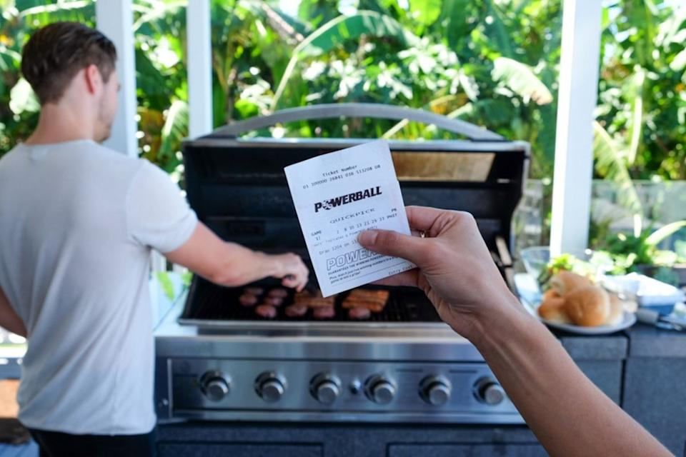 Hand holds up Powerball ticket with man using barbecue in background.