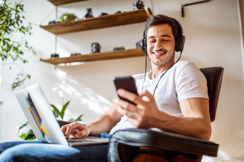 Young man wearing headphones listening to music from mobile phone while working on laptop at home.