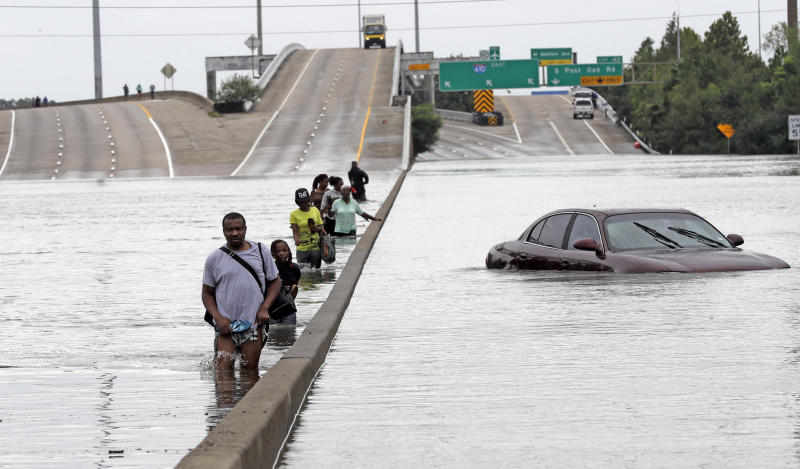Evacuees on a flooded section of Houston's Interstate 610 on Sunday. (AP)