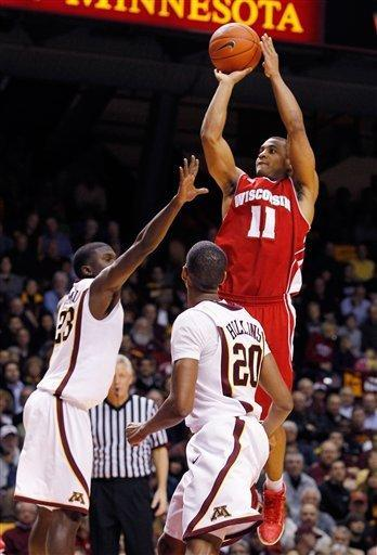 Wisconsin's Jordan Taylor (11) scores over Minnesota's Chip Armelin (23) as Minnesota's Austin Hollins (20) watches during the first half of an NCAA college basketball game Thursday, Feb. 9, 2012, in Minneapolis. Taylor had a game-high 27 points as Wisconsin won 68-61 in overtime. (AP Photo/Genevieve Ross)