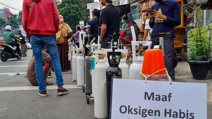 Signage that reads 'sorry, out of oxygen' is seen as people queue outside an oxygen refilling shop
