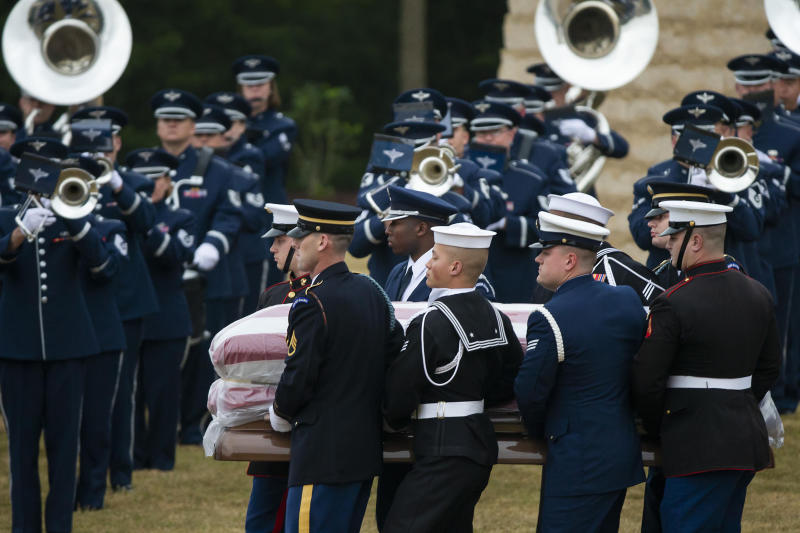 The flag-draped casket of former President George H.W. Bush is carried past a military band to a burial plot close to his presidential library for internment in College Station, Texas, Thursday, Dec. 6, 2018. (Smiley N. Pool/The Dallas Morning News via AP, Pool)