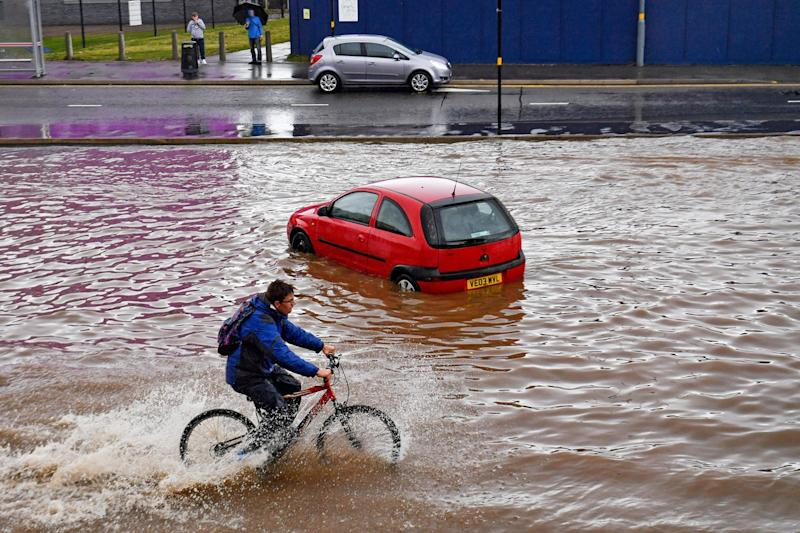 A man cycles past a stranded car on a flooded road in Birmingham