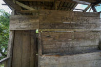 Message written by migrants are seen on the wooden walls of an abandoned house near to the Rio Chucunaque, in Penitas, Darien province, Panama, Friday, Oct. 1, 2021. (AP Photo/Arnulfo Franco)