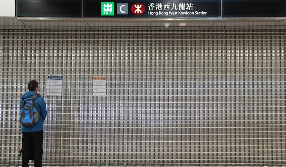 A commuter reads the notice on the gate at the closed West Kowloon station. Photo: Winson Wong