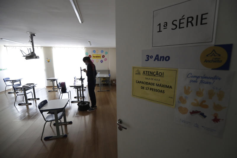 A teacher prepares her classroom at a private school in Brasilia, Brazil, Monday, Sept. 21, 2020. Private schools, closed since the second half of March due to the COVID-19 pandemic, have reopened their doors. Returning to school is optional and online classes continue for students who choose to stay at home watching classes via remote education. (AP Photo/Eraldo Peres)