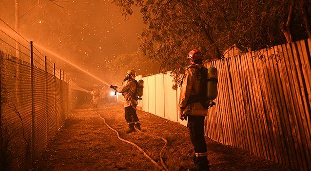Firefighters fight flames close to homes in Corryton Court, Wattle Grove in Sydney, on Saturday. Source: AAP