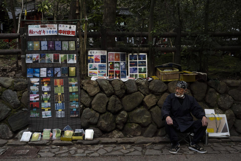 """Artist Kinji Kimura, 76, who sells postcard-sized prints of work, sits on a stool while waiting for customers near the Arashiyama Bamboo Forest in Kyoto, Japan, March 18, 2020. """"Arashiyama is empty,"""" is a new catchphrase that appeared on posters in the area. """"It's time to visit Kyoto,"""" they say, because there are no long lines and waiting to do river rafting, get into popular temples or cross the bridge. (AP Photo/Jae C. Hong)"""
