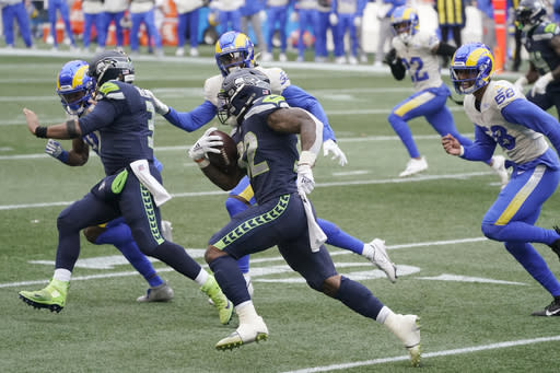 Seattle Seahawks quarterback Russell Wilson, second from left, blocks for running back Chris Carson on a carry by Carson against the Los Angeles Rams during the first half of an NFL wild-card playoff football game, Saturday, Jan. 9, 2021, in Seattle. (AP Photo/Ted S. Warren)
