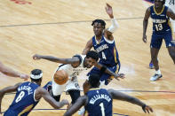 Brooklyn Nets guard Kyrie Irving (11) loses the ball as he drives the lane between New Orleans Pelicans forward Naji Marshall (8), forward Zion Williamson (1) and forward Wes Iwundu (4) in the first half of an NBA basketball game in New Orleans, Tuesday, April 20, 2021. (AP Photo/Gerald Herbert)