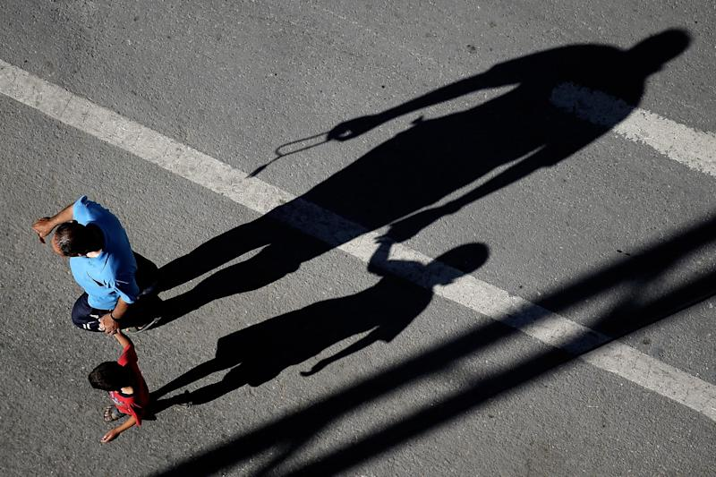 The shadows of a Palestinian father and son are seen in a street in Gaza City on July 17, 2014 (AFP Photo/Thomas Coex)