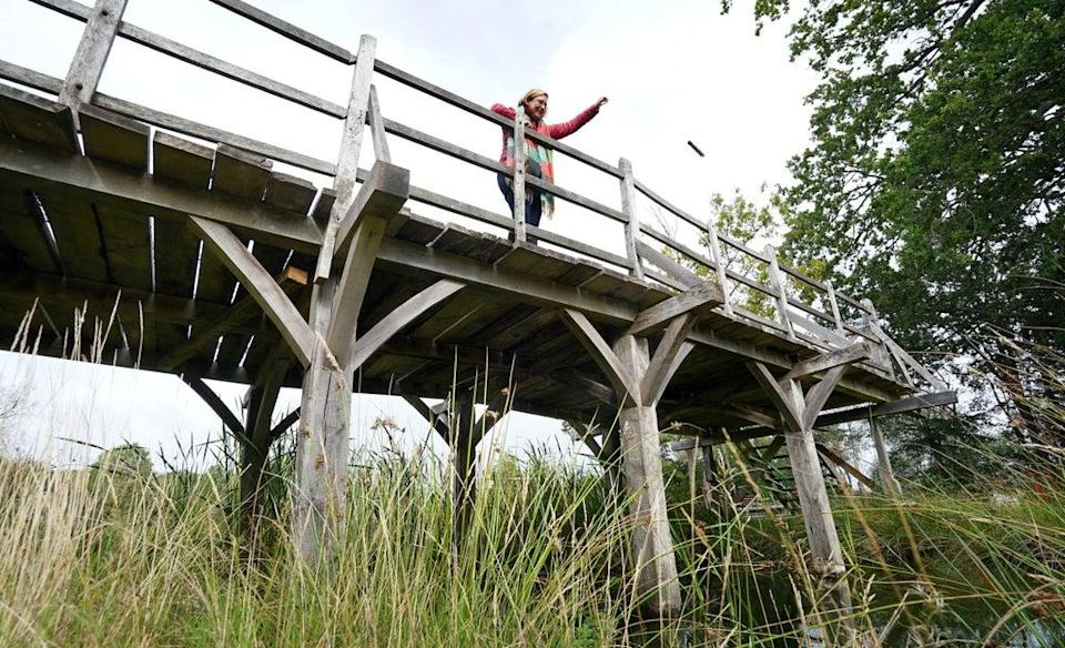 Silke Lohmann, of Summers Place Auctions, stands on the original Poohsticks Bridge from East Sussex's Ashdown Forest, made famous in AA Milne's Winnie the Pooh stories (Gareth Fuller/PA) (PA Wire)