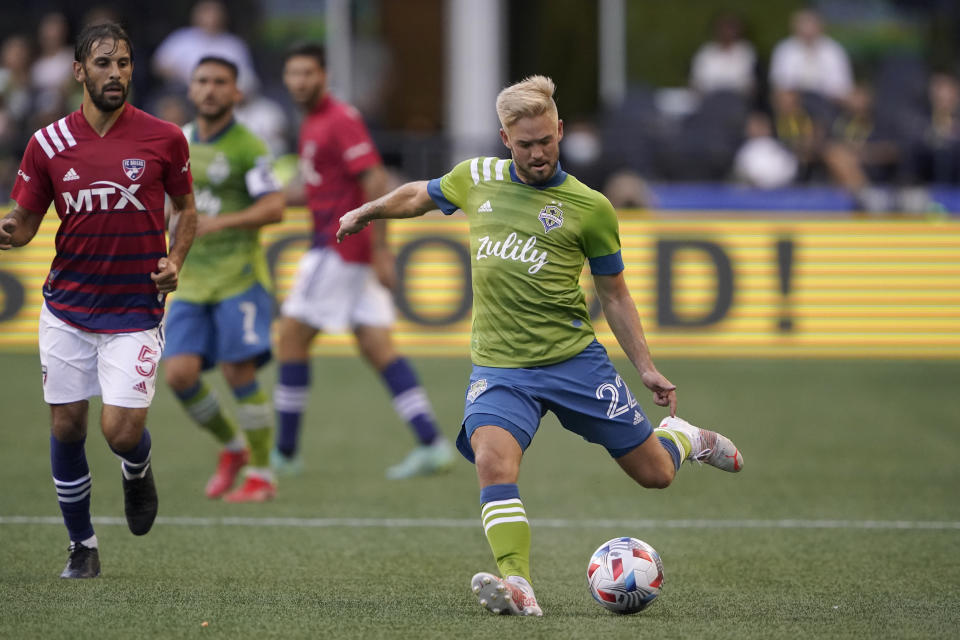 Seattle Sounders midfielder Kelyn Rowe (22) kicks the ball as FC Dallas midfielder Facundo Quignon (5) defends during the first half of an MLS soccer match Wednesday, Aug. 4, 2021, in Seattle. (AP Photo/Ted S. Warren)