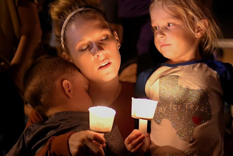 A woman and her children take part in a vigil for victims of a mass shooting in Sutherland Springs.