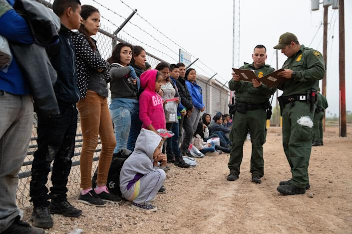 A large group of migrant families wait along the side of the road to be transported after turning themselves in to Border Patrol agents in Penitas, Texas, on Tuesday, Feb. 26, 2019.