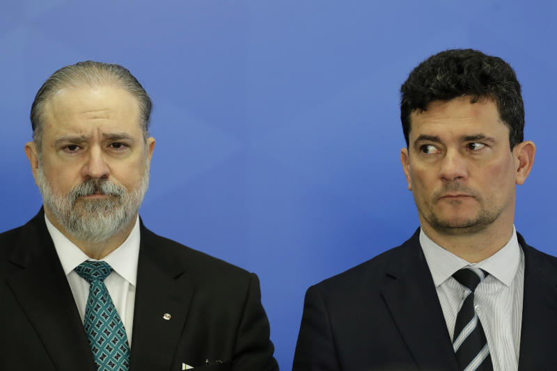 Brazil's new attorney general, Augusto Aras, left, and Minister of Justice Sergio Moro, stand side by side during a swearing-in ceremony for Aras, at Planalto Presidential Palace, in Brasilia, Brazil, Thursday, Sept. 26, 2019. (AP Photo/Eraldo Peres)