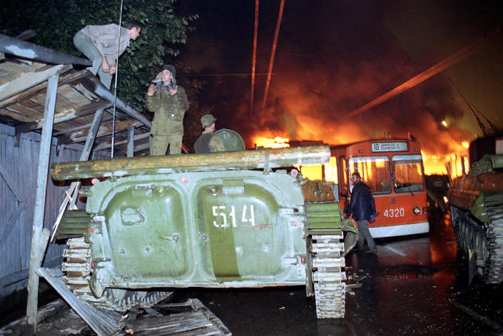 FILE In this Wednesday morning, Aug. 21, 1991 file photo, a trolley bus that was used by anti-coup demonstrators to block the exit of Soviet armored personnel carriers from the area near the Soviet Foreign Ministry office burns during a verbal confrontation between demonstrators and Soviet soldiers standing atop an armored vehicle in downtown Moscow, Russia. When a group of top Communist officials ousted Soviet leader Mikhail Gorbachev 30 years ago and flooded Moscow with tanks, the world held its breath, fearing a rollback on liberal reforms and a return to the Cold War confrontation. But the August 1991 coup collapsed in just three days, precipitating the breakup of the Soviet Union that plotters said they were trying to prevent. (AP Photo/Alexander Zemlianichenko, File)