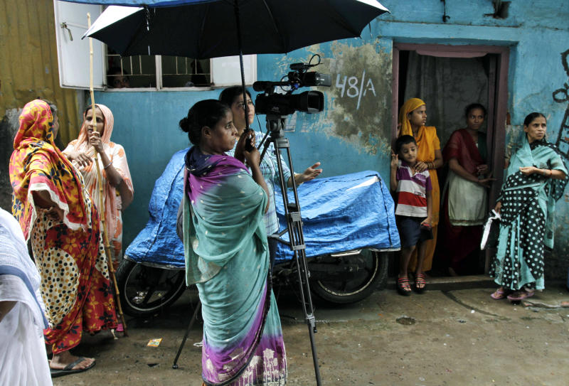 Neighbors of Badar Azim, a 25-year-old footman who gained international fame by helping to announce the birth of Britain's Prince George, watch media activities at the entrance of his house in Kolkata, India, Thursday, Aug. 1, 2013. Azim, who joined Queen Elizabeth II's press secretary at Buckingham Palace's front court on July 22 to post the traditional bulletin announcing the birth of the third in line to the British throne, returned to his home in India on Wednesday after his work visa expired. (AP Photo/Bikas Das)