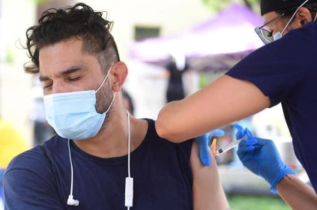 Juan Rodriguez reacts while receiving Johnson & Johnson's Janssen Covid-19 vaccine in Los Angeles, California on August 22, 2021. (Frederic J. Brown/AFP/Getty Images - image credit)