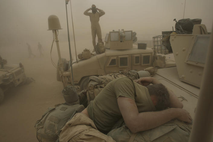 U.S. Marines from the 24th Marine Expeditionary Unit try to take shelter from a sand storm at forward operating base Dwyer in the Helmand province of southern Afghanistan on May 7, 2008. (AP Photo/David Guttenfelder, File)