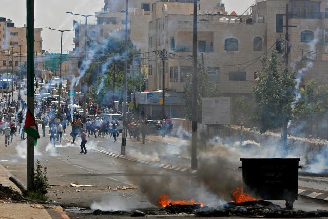 <p>Palestinians throw stones towards Israeli security forces during clashes after a protest marking the 70th anniversary of Nakba — also known as Day of the Catastrophe in 1948 — and against the US' relocation of its embassy from Tel Aviv to Jerusalem, at the main entrance of the occupied West Bank city of Bethlehem on May 15, 2018. (Photo: Musa Al Shaer/AFP/Getty Images) </p>