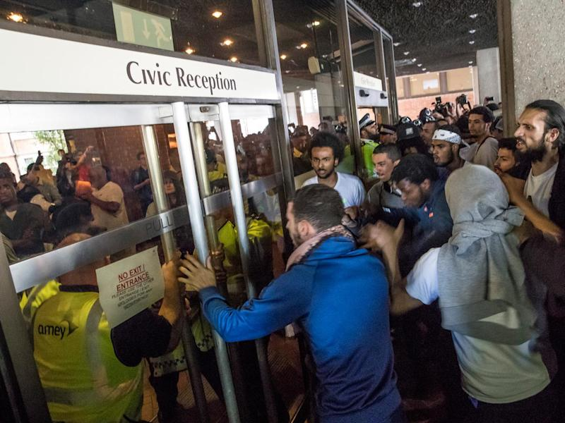 Protesters at Kensington Town Hall yesterday try to force their way into the building (Getty)